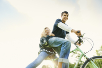 Low angle portrait of young couple on bicycle