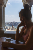 Mid adult woman sitting drinking coffee, looking at view, Budapest, Hungary
