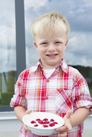 Portrait of boy on patio with bowl of raspberries