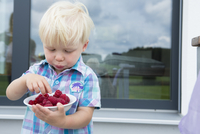 Male toddler on patio eating a bowl of raspberries