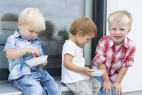 Female toddler and two young brothers on patio eating  bowls of raspberries