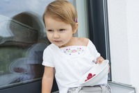 Portrait of female toddler on patio eating  bowl of raspberries