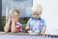 Boy with covering eyes whilst toddler brother eats a  bowl of raspberries