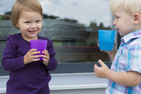 Boy and female toddler drinking from plastic cups on patio