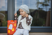 Female toddler sitting on windowsill with home made halloween lantern