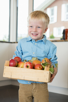 Portrait of boy holding crate of apples