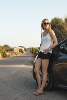Mid adult woman leaning against car at roadside, Menorca, Balearic islands, Spain