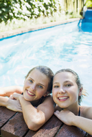 Portrait of two teenage girls leaning on poolside