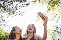 Two teenage girls in park taking smartphone selfie 11015267777| 写真素材・ストックフォト・画像・イラスト素材|アマナイメージズ