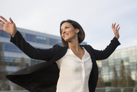 Mature businesswoman celebrating outside office building