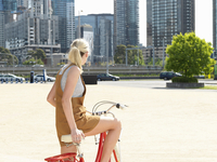 Young woman on bicycle, Southbank, Melbourne, Australia