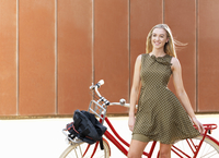 Young woman standing beside bicycle