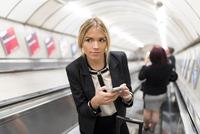 Businesswoman texting on escalator, London Underground, UK