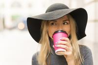 Woman having coffee in street