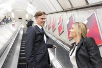 Businessman and businesswoman on escalator, London Underground, UK