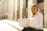 Businesswoman using laptop on kerb, London, UK