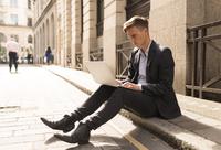 Businessman using laptop on kerb, London, UK