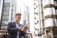 Businessman using digital tablet in street, London, UK