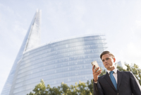 Businessman making call, buildings in background, London, UK