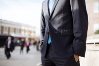 Businessman with hands in pocket, partially obscured, London, UK