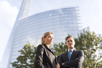 Businessman and businesswoman, buildings in background, London, UK