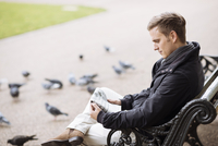 Young man sitting on park bench reading newspaper