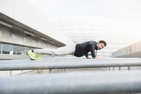 Young male runner doing push ups on handrails in sport arena