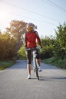 Mature cyclist with bicycle on rural road