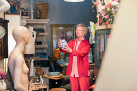 Mature woman examining china pot in vintage shop