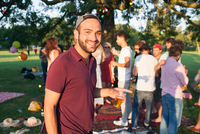 Portrait of young man at crowded party in park at sunset