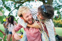 Two male adult friends wrapped in streamers hugging at sunset party in park