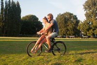 Romantic young couple on bicycle together in park