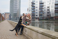 Mid adult woman feeding her dog snacks on riverside wall