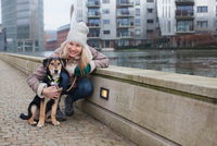 Portrait of mid adult woman and her dog on city riverside