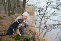Mid adult woman crouching with her dog on riverbank