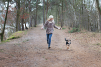 Mid adult woman running with her dog in forest