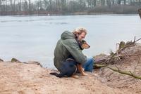 Mature man hugging dog on riverbank