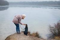 Mid adult woman petting her dog on riverbank