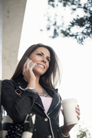 Woman outdoors, using smartphone, holding coffee cup