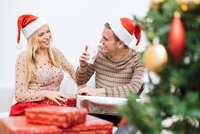 Young man drinking coffee with girlfriend surrounded by christmas presents