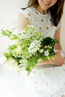 Mature woman wearing white broderie anglaise dress holding flower arrangement smiling