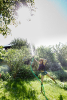 Front view of mature woman in garden standing on one leg squirting water into air with hosepipe