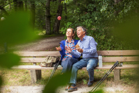 Couple sitting on bench in forest, woman throwing apple in air