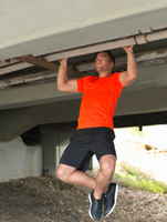 Young man doing pull ups under bridge