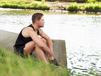 Young man in sports sitting on riverbank