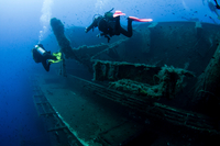 Underwater rear view of divers investigating MS Zenobia shipwreck, Larnaca, Cyprus