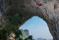 Low angle view of rock climber on Moon Hill, Yangshuo, Guangxi Zhuang, China