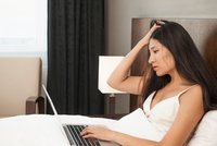 Mid adult woman working on laptop in bed