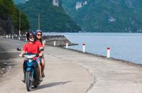 Couple riding motorbike beside bay, Cat Ba Island, Halong Bay, Vietnam