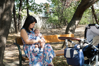 Grandmother sitting on park bench with baby granddaughter
